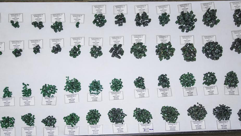 "Visit in 2014 to the Gemfields Kagem Mine in Zambia. A ""Master Sample Table"" contains like groupings representing Gemfields' various emerald grades. Meanwhile, various assorted emerald piles await meticulous sorting prior to auction."